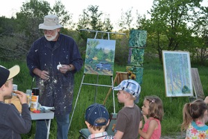 Visual Artist Ron Walker chats with the children while painting the landscape