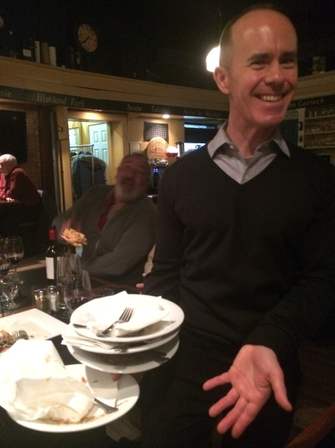 Our waiter Jan holding all of our empty dishes.