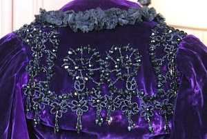 Intricate jet beading adorns the back of this purple silk velvet caplet from 1895.