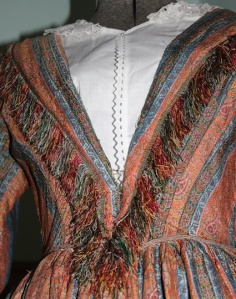 A woollen dress is woven in a stripe design of blue and orange with silk fringe.