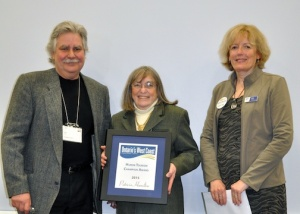 Huron County Museum and Historic Gaol Curator Patricia Hamilton (centre) receives the Tourism Champion Award from past recipient Jim Lee of Cinnamon Jim's and Huron County Tourism Co-ordinator Cindy Fisher.